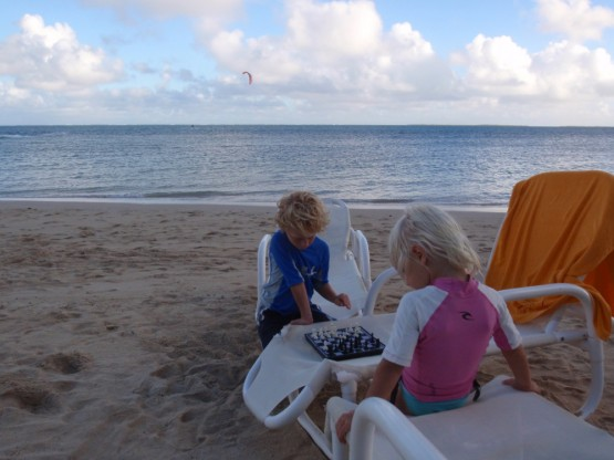 playing chess on the beach, Mami kiting in the background